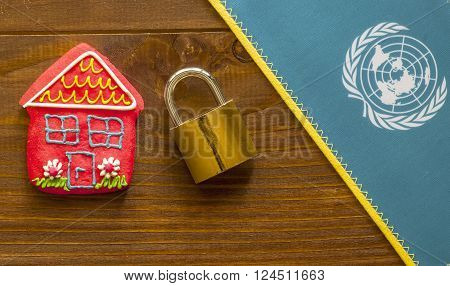 Red sweet house padlock and United Nation flag on wooden background. Concept of International Safe House