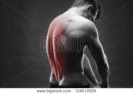 Man with backache. Pain in the human body. Muscular male body. Handsome bodybuilder posing on gray background. Black and white photo with red dot