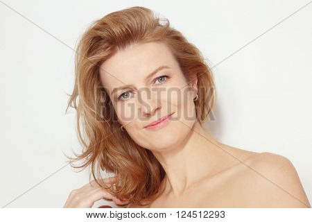 Portrait of beautiful healthy happy smiling mature woman with curly hair and clean make-up