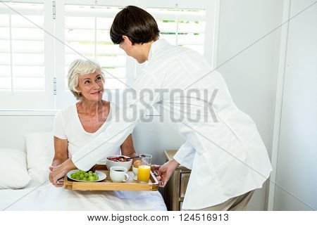 Female caregiver serving breakfast to senior woman at home