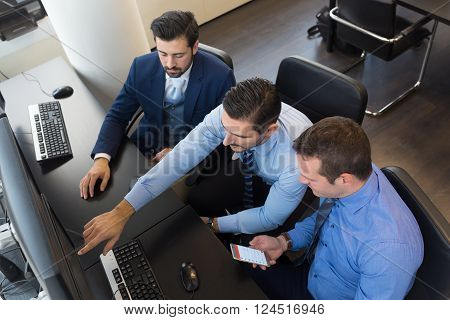 Businessmen trading stocks. Stock traders looking at graphs, indexes and numbers on multiple computer screens. Colleagues in discussion in traders office. Business success concept.