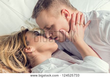 Close-up of kissing young couple in bed.