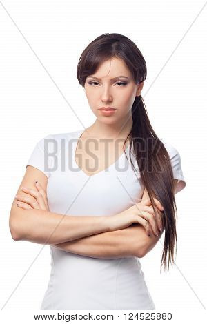 Angry young woman with crossed arms on white background