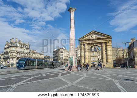 Bordeaux France - March 26 2016. Tram rolling near to Porte d'Aquitaine (local name) Aquitaine gate at Place de la Victoire. To the left the monument to the wine. Bordeaux France.
