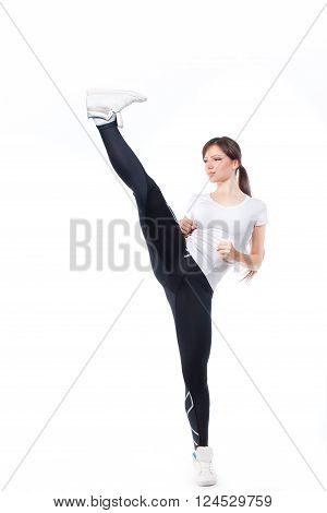 Woman practicing tae-bo exercises, kicking forward with legs. Photo set of sporty female brunette girl wearing sports clothes over white background