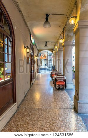 Bologna, Italy - December 27, 2015: day view of Bologna's passage way with reataurant tables. In total there are about 38 kilometres of arcades in the city's historical centre In Bologna Italy.
