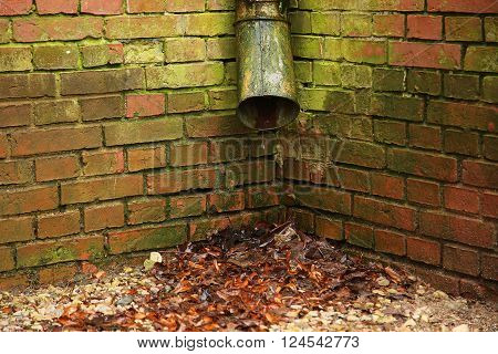 downspout with background of a red brick wall
