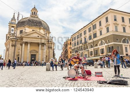 ROME, ITALY - MAY3, 2015: People playing music in the Piazza del Popolo. The big square takes its name from the church Santa Maria del Popolo and it always hosts different type of artists.
