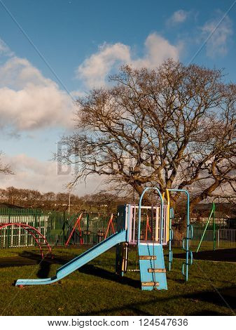 An empty park containing a slide swings and climbing frame.