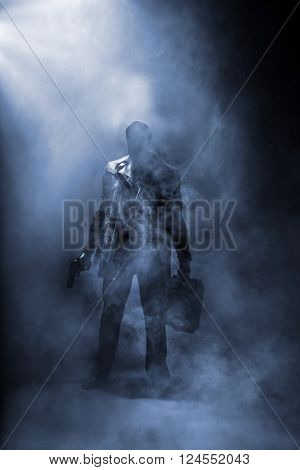 Faceless man holding a gun and a briefcase standing in haze.