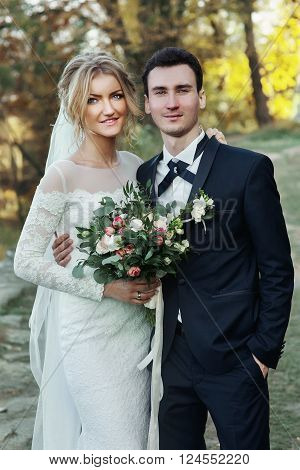 Gorgeous Blonde Bride With Bouquet & Handsome Groom Posing Near Old Castle
