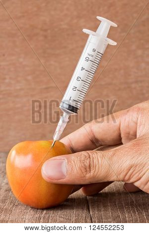 Fresh tomato and syringe with hand holding on a wooden table