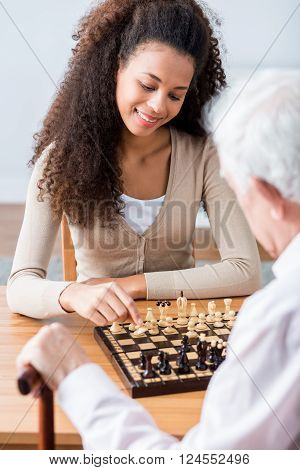 Young pretty happy carer plying chess with her older ward poster