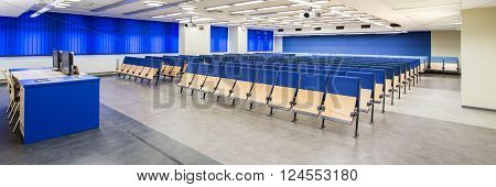 Modern big university with spacious lecture hall with blue chairs and marble floor