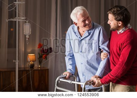 Photo of son supporting disabled father with zimmer