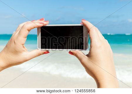 Woman Holds Phone For Taking Beach Photo