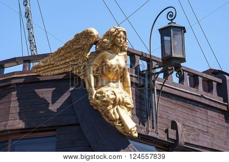 Sitting golden caryatid with wings in the big wooden sailing ship