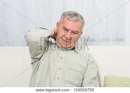 Senior man is sitting on sofa and having neck pain.