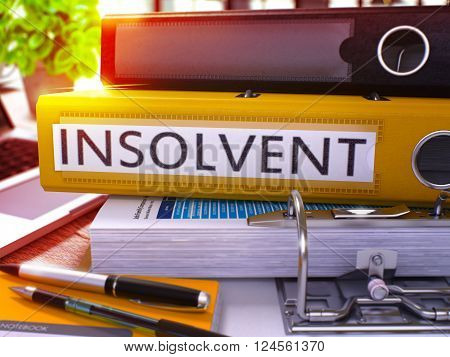 Yellow Ring Binder with Inscription Insolvent on Background of Working Table with Office Supplies and Laptop. Insolvent Business Concept on Blurred Background. 3D Render.