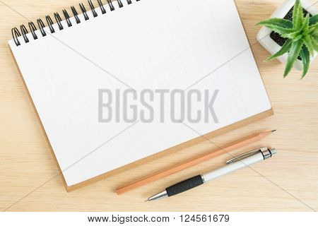 Top view of office desk table with open spiral notebook pencil and small tree in a white pot on wood table