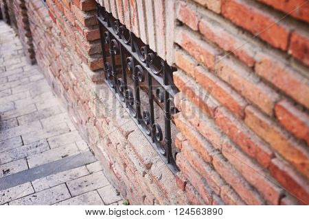 Ancient Brick Wall And Window Locked With Metal Bars