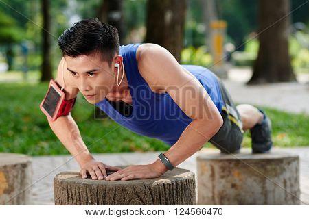 Sweaty determined young Vietnamese sportsman doing push-ups