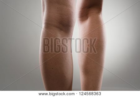 Close up of woman's leg calves over grey background. Muscular hurt and rheumatism concept.Young Caucasian female suffering from pain in legs.