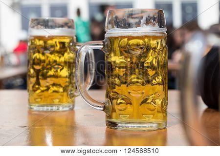Two Beer Glasses In German Biergarten Background