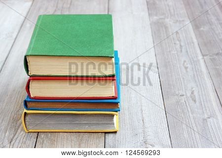 Four books in the colored cover on the table made of boards.