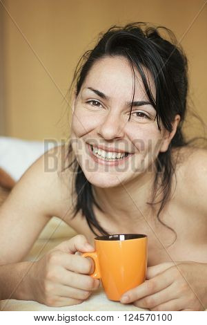 Smiling girl in morning waking with coffee cup in hands, happy expression, wellness and health concept