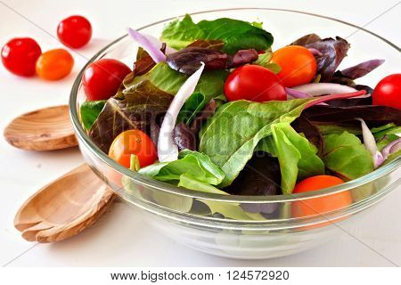 Garden Salad With Cherry Tomatoes And Red Onions In Clear Bowl Close Up On White Wood