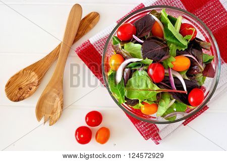 Mixed Salad With Cherry Tomatoes And Red Onions In Clear Bowl Overhead Scene On White Wood