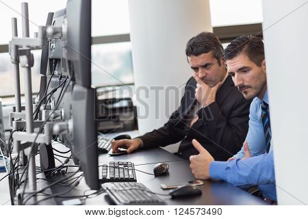 Thoughtful businessmen trading stocks in corporate office.. Concerned stock traders looking at graphs, indexes and numbers on multiple computer screens. Business crisis and loss concept.