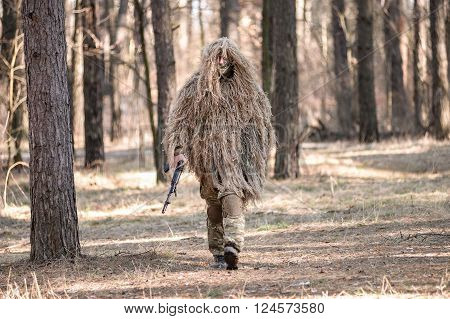 Soldier in camouflaged sniper suit walking with gun in forest.Selective focus.