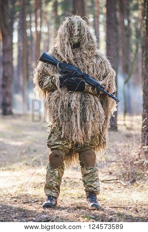 Soldier in camouflaged sniper suit standing in forest with rifle in hands.Selective focus.