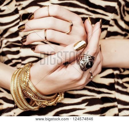 woman hands with golden manicure lot of gold jewelry on fancy dress close up