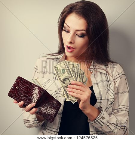 Surprising Happy Woman Holding Dollars And Looking In Wallet And Counting Money