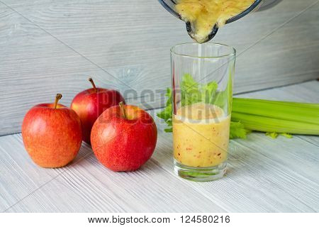 Smoothies Made From Apples And Celery Is Poured Into A Glass From A Food Processor