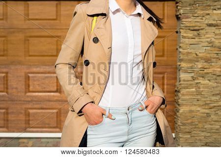 Slender Girl In A Beige Coat, Blue Jeans And White Shirt Outdoors