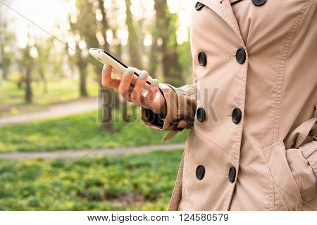 Woman In Beige Coat Walks In The Park And Using A Mobile Phone
