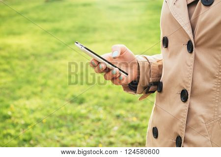 Woman In Beige Coat Walks In The Park And Enjoy A Smartphone