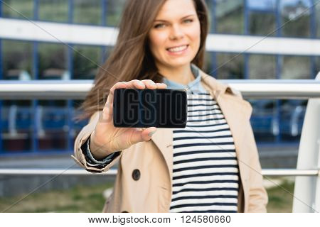Attractive Smiling Woman Shows The Display Of The Smart Phone Outdoors