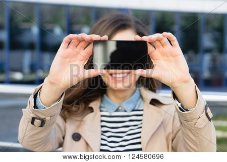 Cute Smiling Woman Shows The Display Of The Smart Phone Outdoors
