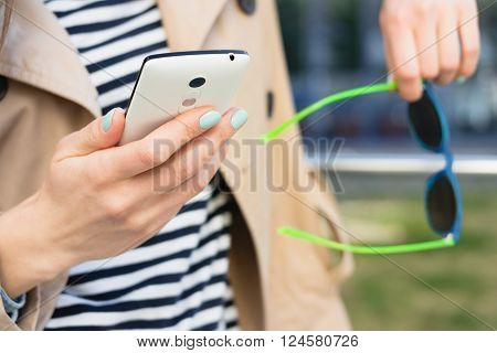 Girl In A Beige Jacket And A Striped Shirt Holding Mobile Phone And Sun Glasses Outdoors