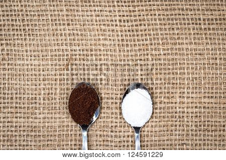 Coffee and sugar on metallic spoons on gunny textile