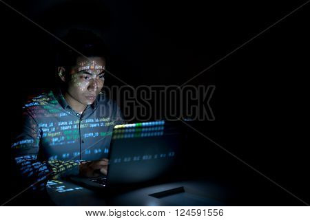 Software developer coding on his laptop at night