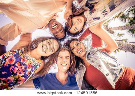 Multicutural group of young people having fun on a tropical beach - Friends on a summer holiday looking down at camera and laughing