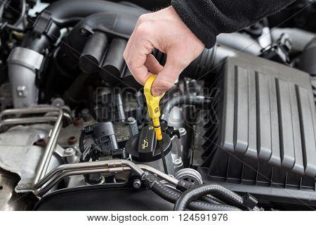Hand Checking Oil Dip Stick In Modern Car Motor
