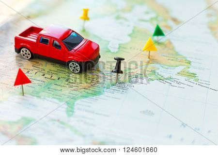 Road trip - car goes on map across the territory of the USA. The route of automobile travel is laid by office pins. Planning active vacation interesting journey.