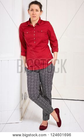 Young woman in red shirt lean against wall